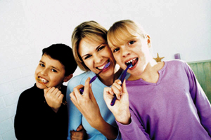 Mother, son, and duaghter brushing their teeth